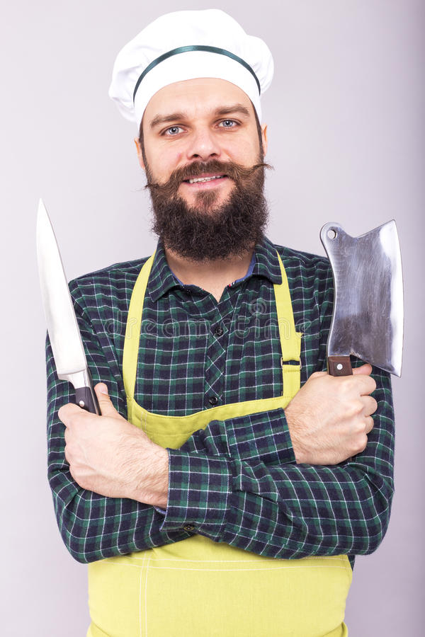Atelieraufnahme eines glücklichen bärtigen jungen Mannes, der scharfe Messer hält lizenzfreies stockfoto