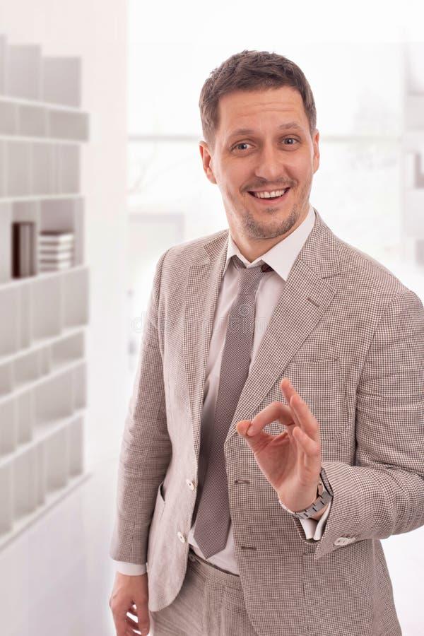 Atelieraufnahme eines jungen Mannes, der den beige Anzug gibt Ihnen eine anerkennend Geste gegen einen whait Hintergrund trägt lizenzfreies stockfoto
