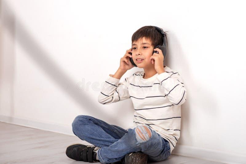Atelieraufnahme eines Jungen mit den Kopfhörern, die auf dem Boden durch die Wand stationieren und Musik hören stockfoto