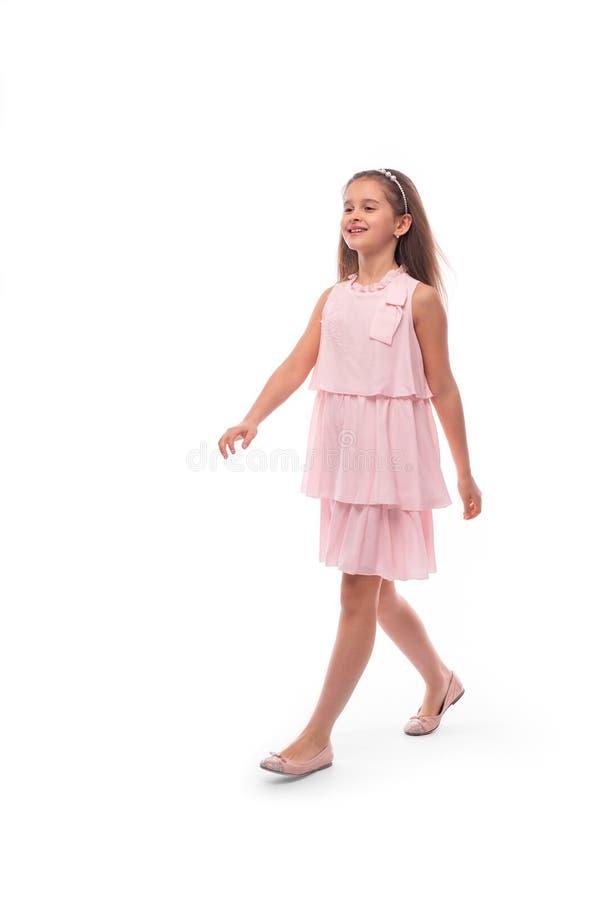 Atelieraufnahme eines kleinen lächelnden Mädchens, das rosa sundress auf einem weißen Hintergrund trägt Sie geht mit einer guten  lizenzfreie stockfotos