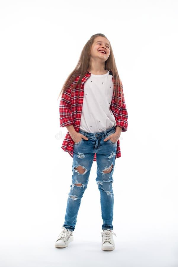 Atelieraufnahme eines lächelnden Mädchens, das in den Jeans und in einem roten überprüften Hemd auf einem weißen Hintergrund träg stockfotos