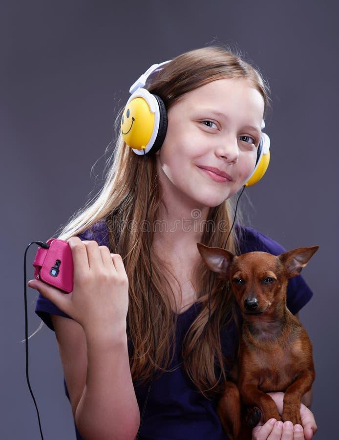 Atelieraufnahme eines lächelnden jugendlich Mädchens mit Kopfhörern und Hündchen stockfotos