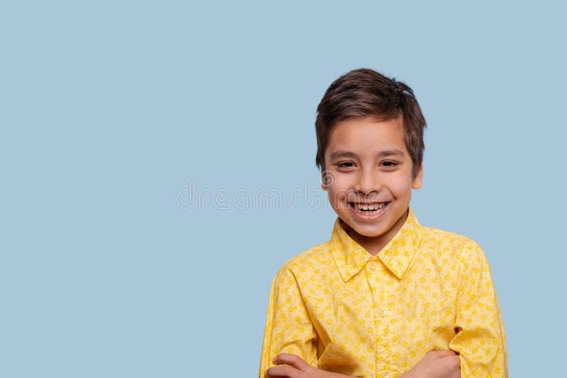Atelieraufnahme eines lächelnden Jungen, der gelbes T-Shirt auf einem blauen Hintergrund mit Kopienraum trägt stockfoto