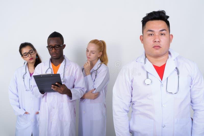 Atelieraufnahme jungen asiatischen Manndoktors mit verschiedener Gruppe mult lizenzfreie stockfotos