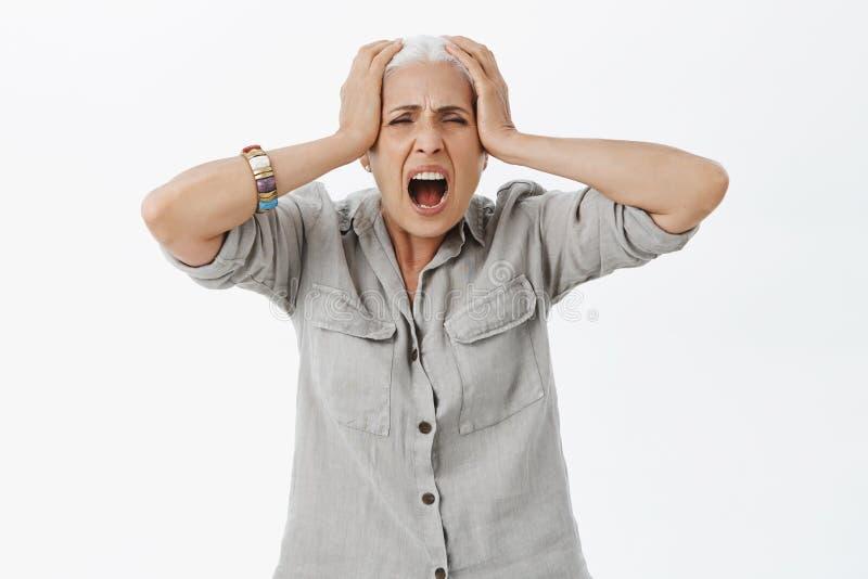 Atelieraufnahme von disstressed verlierendes Temperament der gereizten und älteren Frau, das heraus lautes vom Schmerz- und Krise lizenzfreies stockfoto