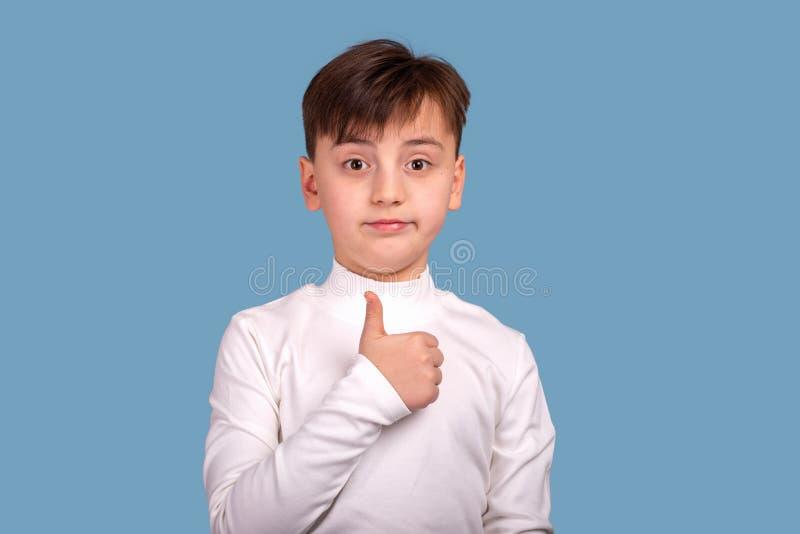 Atelieraufnahmeporträt eines Jungen, der ein weißes Hemd gibt Ihnen eine anerkennend Geste auf blauem Hintergrund trägt lizenzfreie stockfotografie