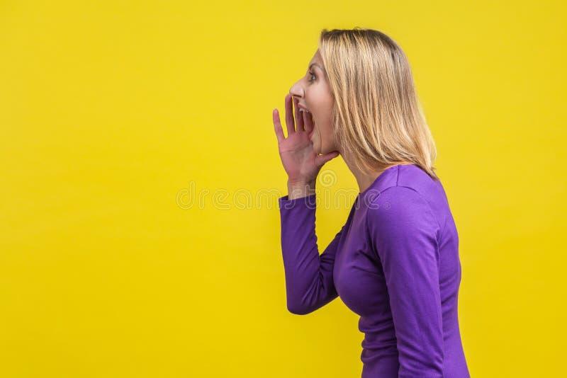 Atenção! vista lateral de uma mulher agressiva gritando anúncio sobre fundo amarelo fotografia de stock