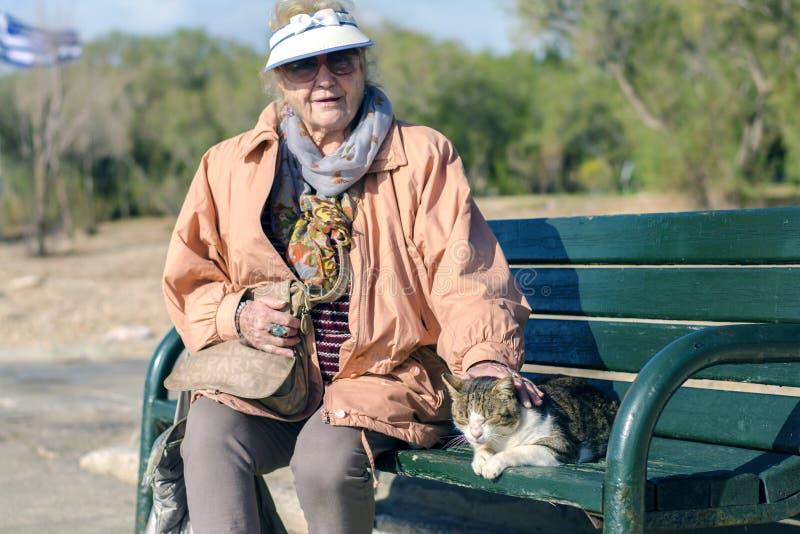 Aten Grekland - December 16 2018 en äldre kvinna och en hemlös katt royaltyfri foto