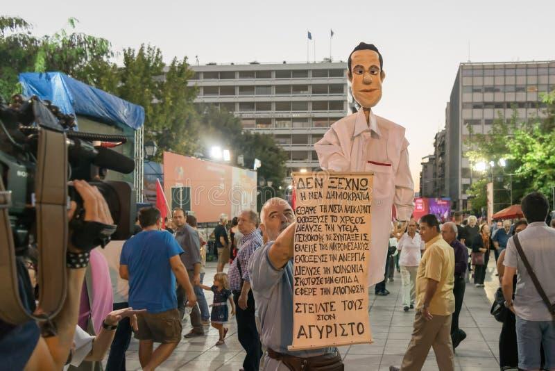 Aten Grekland 18 September 2015 Protestant med en karikatyr av Alexis Tsipras som ger en intervju till en lokal kanal fotografering för bildbyråer