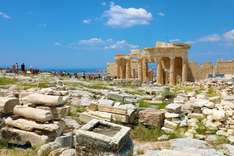 ATENAS, GRÉCIA - 18 DE JULHO DE 2018: a vista bonita das ruínas no monte da acrópole com os turistas que visitam e atravessa afas fotografia de stock