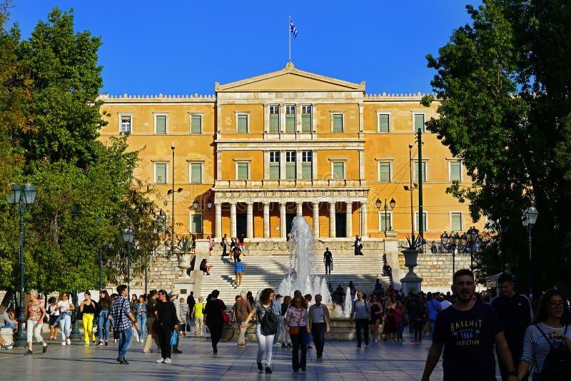 Atenas, Grécia - 6 de outubro de 2014 pessoa que anda no quadrado do Syntagma com a construção grega do parlamento como um fundo fotografia de stock