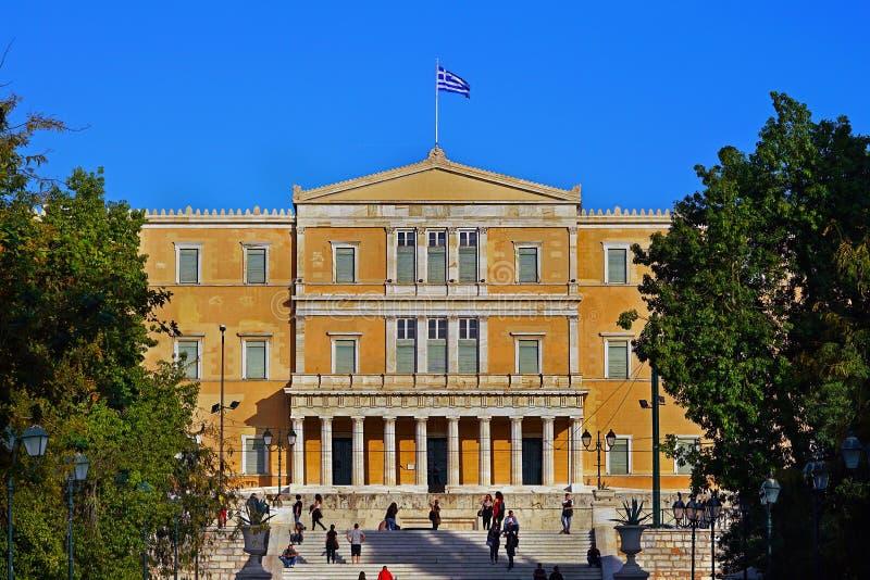 Atenas, Grécia - 6 de outubro de 2014 pessoa que anda no quadrado do Syntagma com a construção grega do parlamento como um fundo fotos de stock royalty free