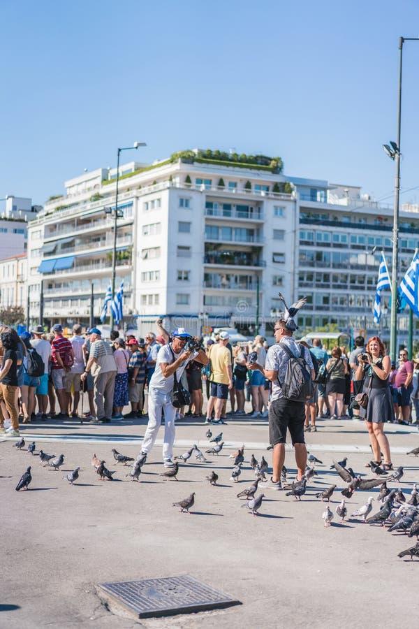 ATENAS, GRÉCIA - 16 DE SETEMBRO DE 2018: Poses da criança com os pombos e as mulheres bonitas que sorriem a ele no parlamento gre imagens de stock royalty free