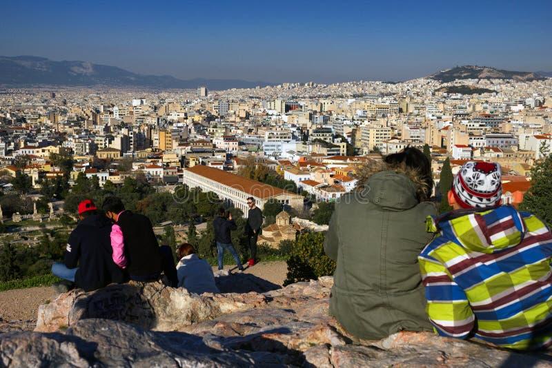 Atenas, Grécia, o 30 de janeiro de 2018: Os povos apreciam a vista à cidade de Atenas do monte de Areopagus fotografia de stock royalty free