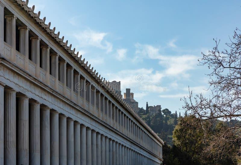 Atenas Grecia Columnas de la fachada del stoa de Attalus, fondo de la roca de la acrópolis, cielo azul, día soleado foto de archivo
