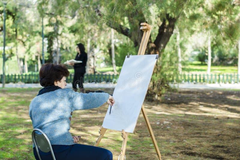 Atenas, Grecia - 16 de diciembre 2018 el artista dibuja una imagen con un lápiz fotos de archivo