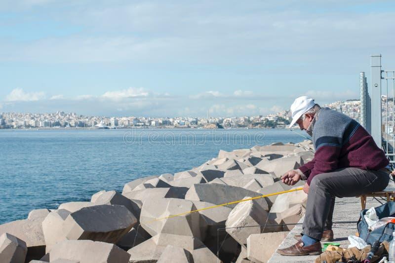 Atenas, Grecia 16 de diciembre El pescador 2018 coge pescados del rompeolas fotografía de archivo libre de regalías