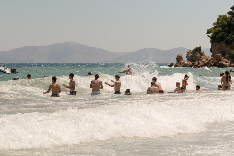 Atenas, Grecia 19 de julio de 2015 Gente que juega con las ondas grandes en una playa fotografía de archivo libre de regalías