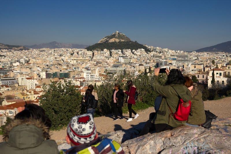 Atenas, Grecia, el 30 de enero de 2018: La gente disfruta de la visión a la ciudad de Atenas de la colina de Areopagus fotos de archivo libres de regalías