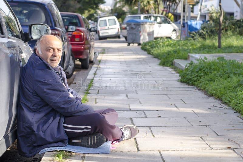 Atenas, Grecia/mendigo de diciembre 17,2018 pide limosnas en las calles de Atenas a lo largo del camino estorbado con los coches fotografía de archivo libre de regalías