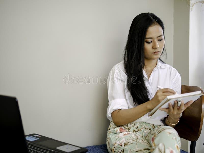Atención hermosa asiática de la paga del freelancer para tomar abajo notas, la escritura o el concepto de la creatividad del dibu imagenes de archivo