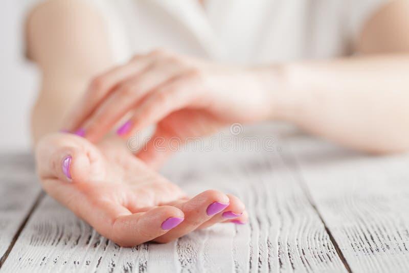 Atención sanitaria de la medicina Mano femenina que comprueba pulso en el primer de la muñeca imágenes de archivo libres de regalías