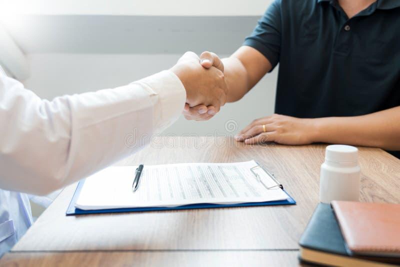 Atención sanitaria de la medicina y concepto de la confianza, doctor que sacude las manos con el colega paciente después de habla imagen de archivo