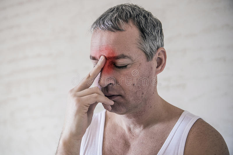 Atención sanitaria, dolor, tensión, edad y concepto de la gente - hombre maduro que sufre de dolor de cabeza en casa imagen de archivo