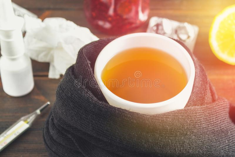 Atención sanitaria, medicina tradicional y concepto de la gripe - taza de té con el limón, el termómetro y las drogas en la tabla fotos de archivo libres de regalías