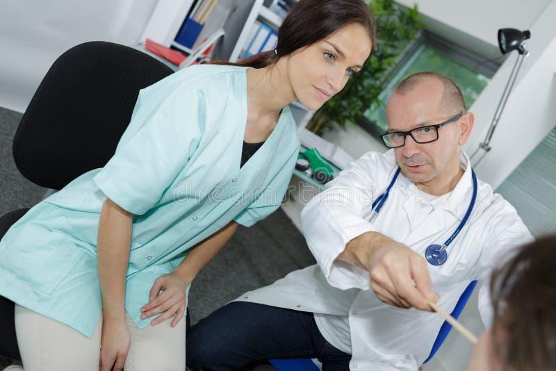 Atención sanitaria y concepto médico - doctor y enfermera con el paciente imagen de archivo