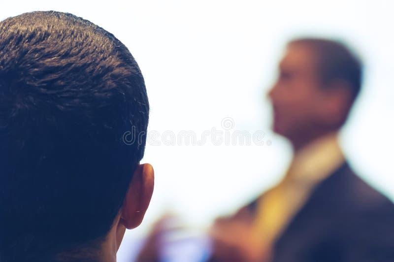 Atendee masculino que escuta o orador masculino que dá uma conversa no treinamento do seminário da TI fotografia de stock royalty free