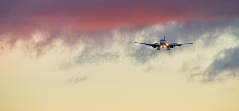 Aterrissagem comercial do avião do avião no por do sol foto de stock