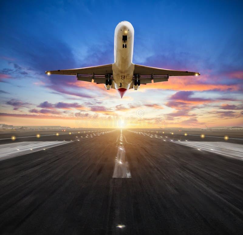 Aterrissagem de avião à pista de decolagem do aeroporto na luz do por do sol imagens de stock royalty free