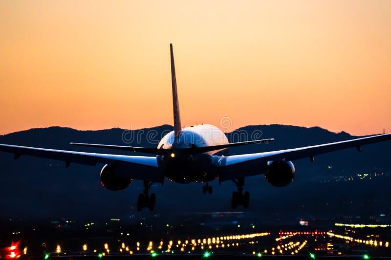 Aterrissagem de avião ao aeroporto no crepúsculo imagem de stock
