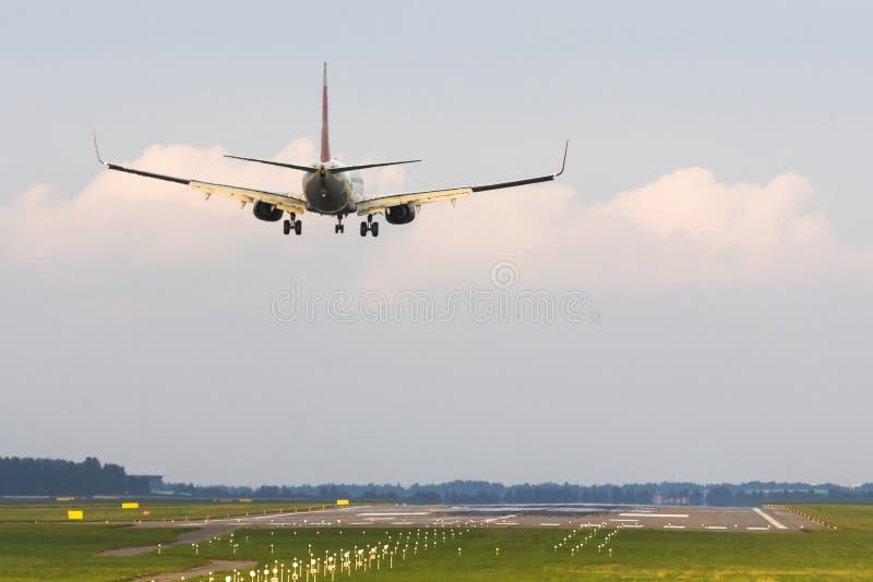 Aterrissagem de avião dos passageiros ao aeroporto Vista da pista de decolagem da extremidade fotografia de stock royalty free