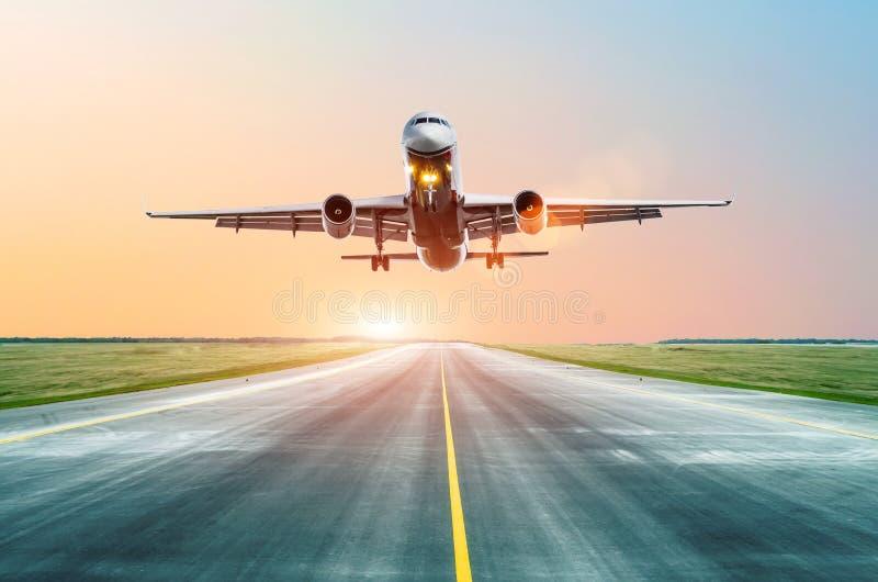 Aterrissagem de avião na pista de decolagem na noite no por do sol no aeroporto imagem de stock