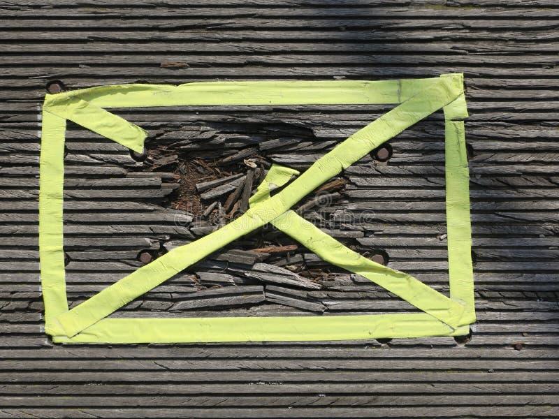 Aterrissagem de madeira com um orifício marcado com fita amarela imagens de stock royalty free