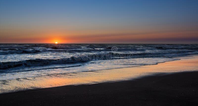 Aterrissagem, sol que ajusta o mar excedente e irritado imagem de stock