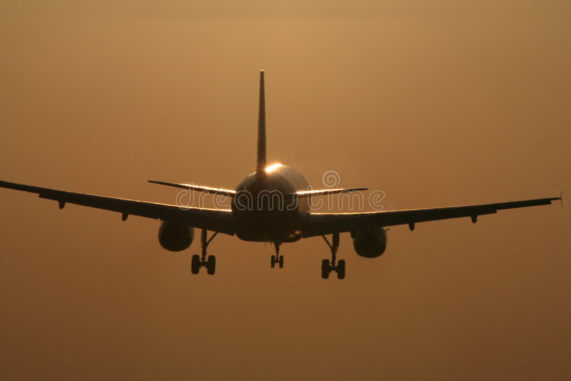 Aterrizaje de aviones en la puesta del sol fotos de archivo libres de regalías