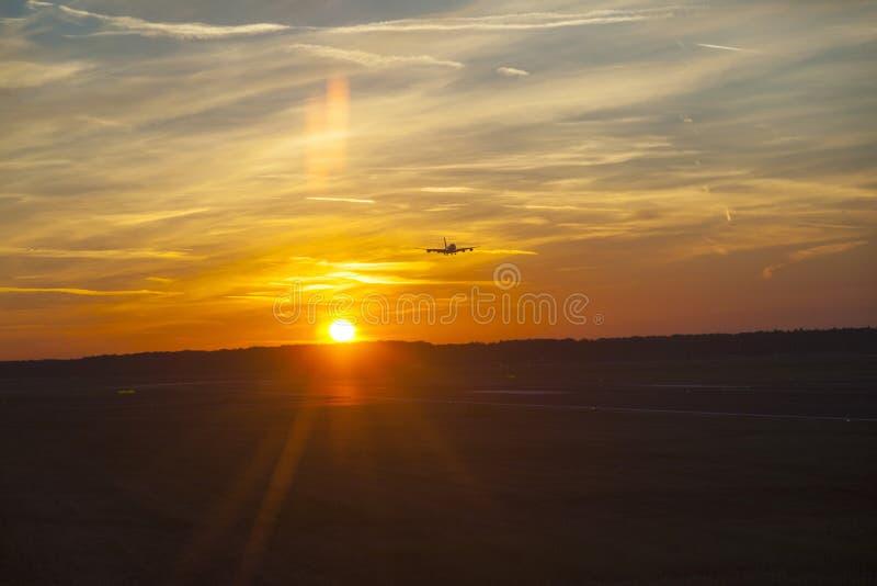 Aterrizaje de aviones en puesta del sol imagen de archivo