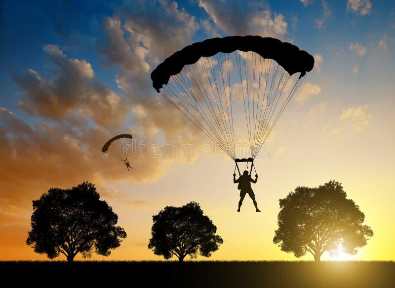 Aterrizaje del paracaidista en la puesta del sol fotografía de archivo libre de regalías