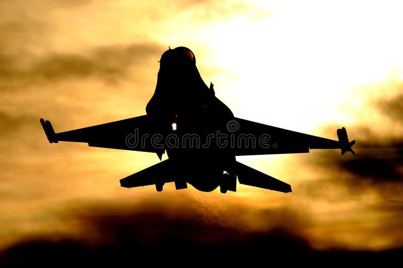 Aterrizaje F-16 en la puesta del sol fotografía de archivo libre de regalías