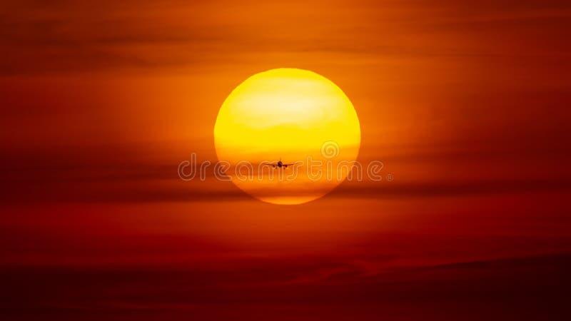 Aterrizaje o despegue de aeroplano en la puesta del sol con el cielo rojo en el aeropuerto internacional de Bucarest, localizació imagen de archivo