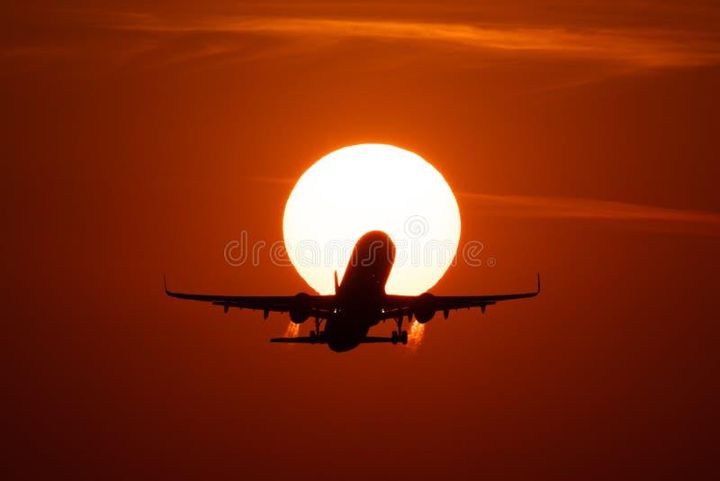 Aterrizaje o despegue de aeroplano en la puesta del sol con el cielo rojo en el aeropuerto internacional de Bucarest, localizació imagenes de archivo