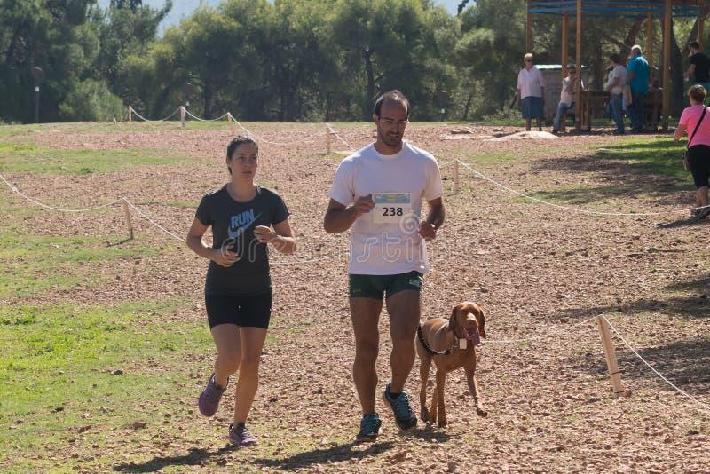 Athènes, Grèce le 4 octobre 2015 L'homme et la fille courant à la concurrence de famille courent avec votre chien en Grèce photographie stock