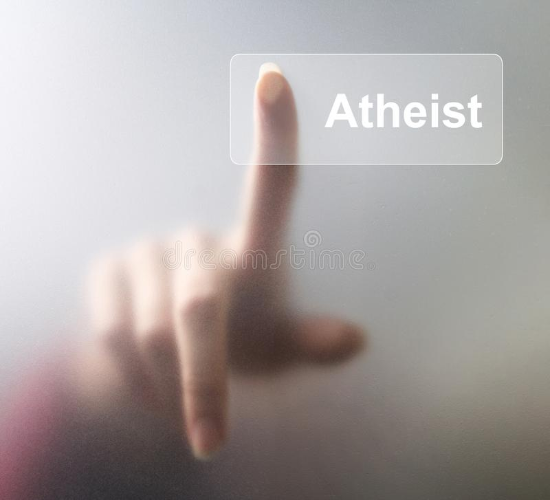 Atheist button. Woman finger pressing a glass atheist button on grey background.  royalty free stock photos