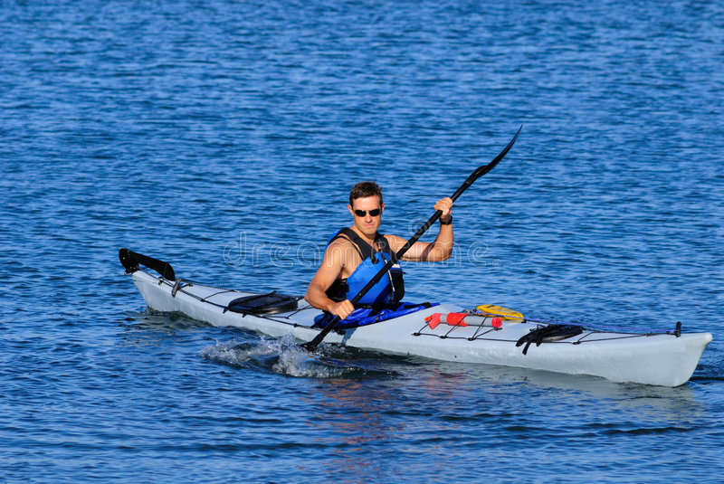 Atheltic man kayaking in Mission Bay. Atheltic man is kayaking in cal blue waters of Mission Bay, San Diego, Califronia. Copy space on top stock photography