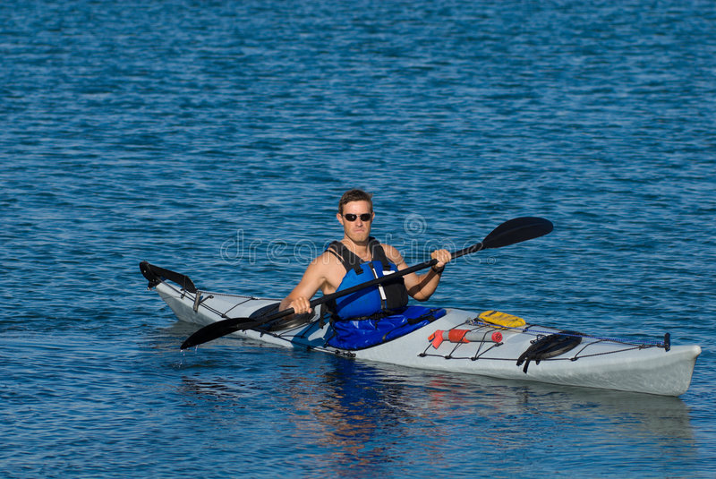 Atheltic man in a sea kayak royalty free stock photography