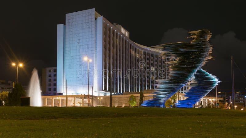 Athene, Griekenland 25 November 2015 Athene 's nachts tegen het agentstandbeeld en een modern gebouw stock foto