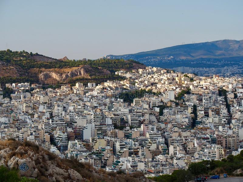 Athens Cityscape of White Buildings on Hillside. Athens cityscape showing white buildings and apartments crowded together on a hill, showing population density royalty free stock photo